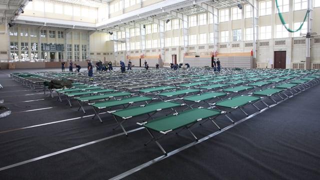 Klappbetten für Flüchtlinge in einer Sporthalle der Universität Leipzig.