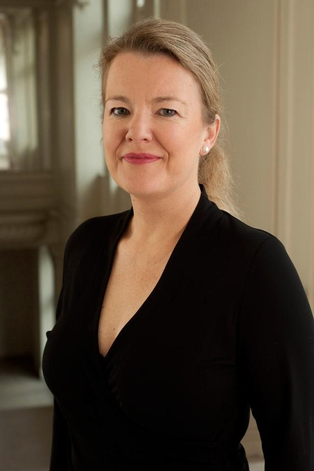 Ilona Schmiel, in schwarzem Oberteil und mit Rossschwanz, blickt lächelnd in die Kamera