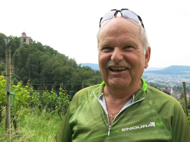 René Schenker posiert freundlich für die Kamerra. Portraitbild im Freien. Man sieht, dass er in Sportkleidern ist-