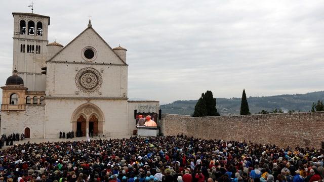 Menschen verfolgen vor der Basilika San Francesco in Assisi die Predigt des Papstes auf einem Bildschirm.