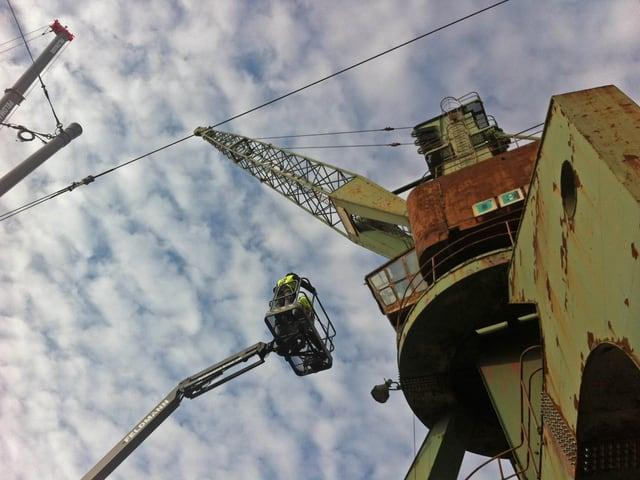 Der Hafenkran ragt in einen trüben Himmel, ein Lift mit zwei Bauleuten nähert sich ihm bedrohlich. Man bemerke die Anthropomorphisierung des Hafenkrans.