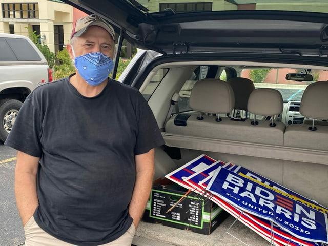 Mann vor dem geöffneten Kofferraum, darin Biden-Harris-Plakate.
