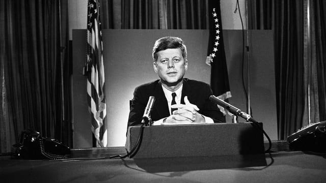 John F. Kennedy in einer TV-Ansprache vor US-Flagge.