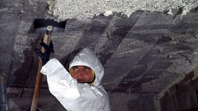 Arbeiter mit Schutzanzug kratzt Asbest von einer Decke.
