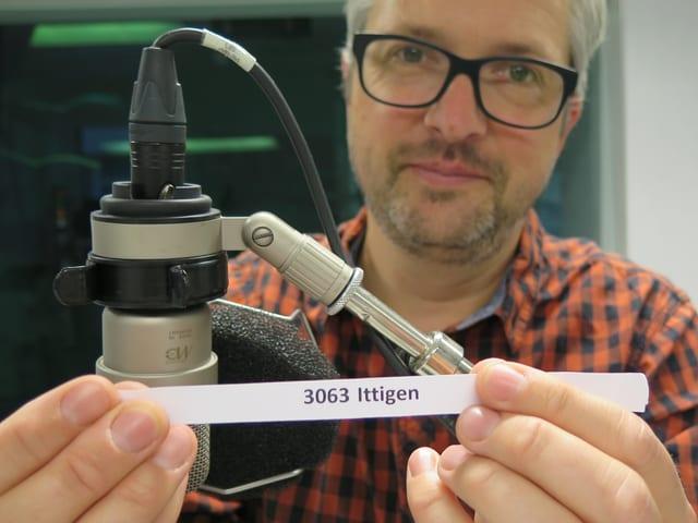 Mann mit Brille hält schmalen Papierstreifen hoch. Darauf steht 3063 Ittigen