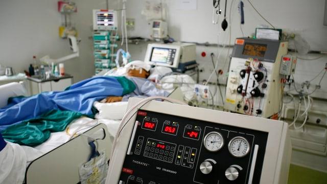 Person in Krankenbett, an Geräte angeschlossen