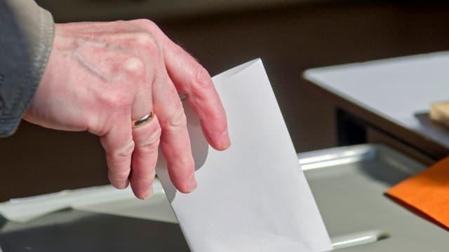 Ein Wahlzettel wird in eine Urne geworfen.