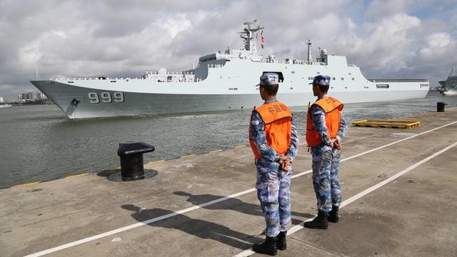 Zwei Soldaten in Tarnanzug und orangen Westen stehen stramm, während ein Kriegsschiff im Hafen vorbeifährt.