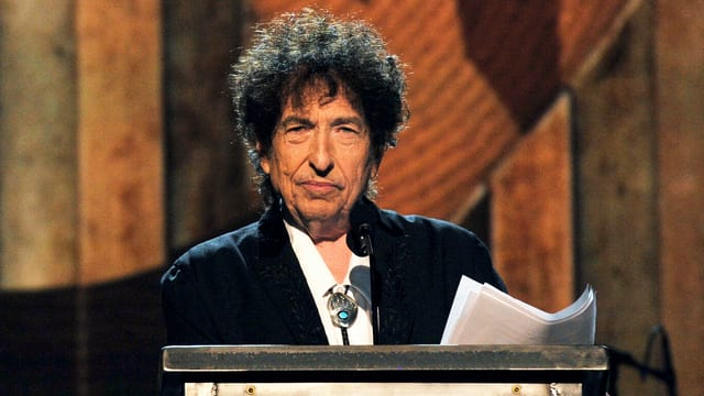 Dylan mit Notizen an einem Rednerpult
