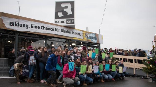 Die Glasbox der Spendenaktion Jeder Rappen zählt in Luzern. Im Vordergrund eine Schulklasse.