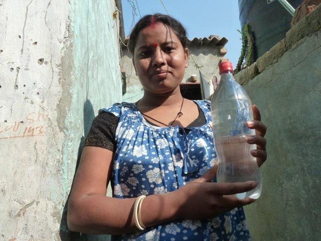 Die 32-jährige Nupur wohnt in einem Slum von Delhi. Sie legt PET-Flaschen an die Sonne, um Wasser zu entkeimen.