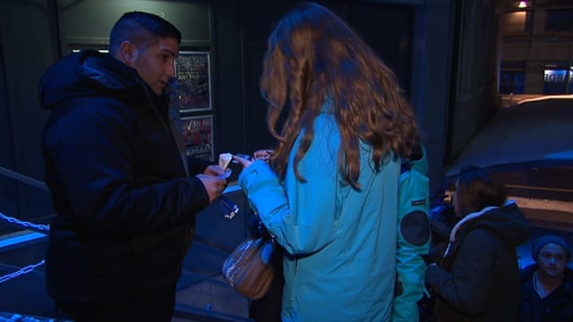 Türsteher kontrolliert Ausweis einer jungen Frau.