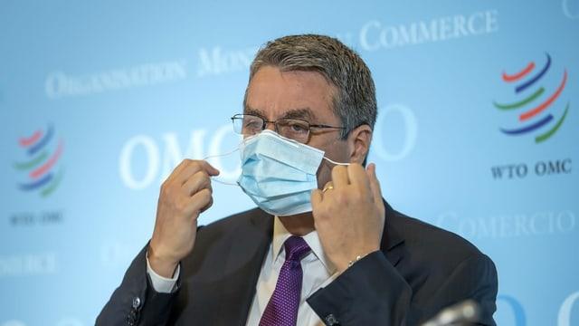 Mann mit Anzug und Krawatte zieht sich eine Schutzmaske über Mund und Nase