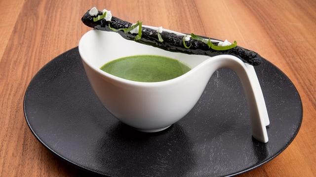Suppenteller mit grüner Suppe und schwarzem Gebäck.