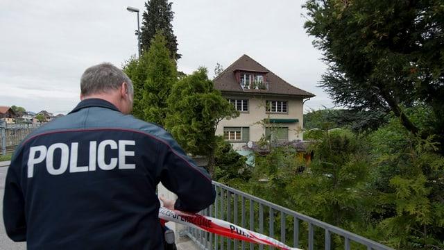 Polizist vor einem Haus