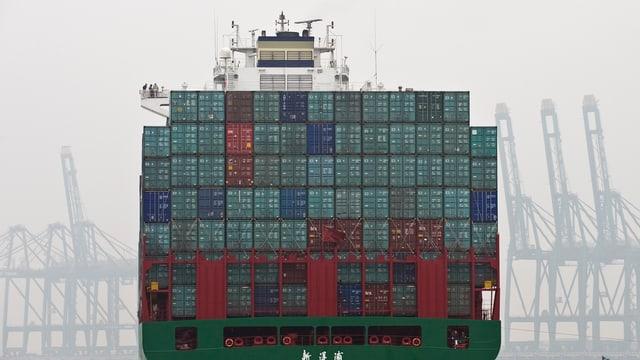 Ein Containerschiff verlässt voll beladen einen Industriehafen.
