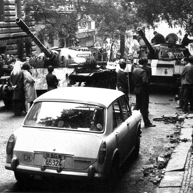 Schwarz-Weiss-Fotografe: Auto mit Aargauer Nummernschild vor Panzer.
