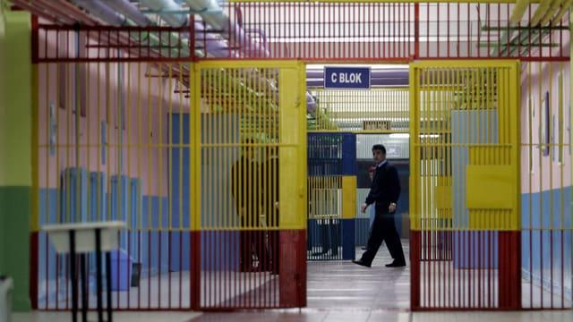 Blick ins Innere eines Gefängnisgangs mit einer offenen Gittertür