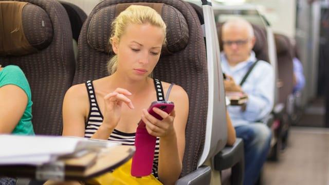 Eine Frau sitzt im Zug und tippt auf ihrem Handy.