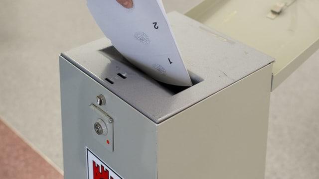 In maun che metta cedels da votar en in'urna.
