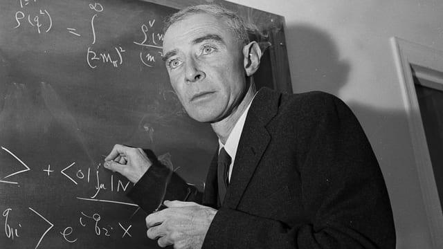 Robert Oppenheimer steht vor einer Wandtafel und schreibt mit Kreide Formeln auf.