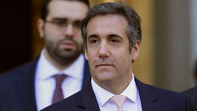 Brustbild von Cohen mit Bodyguard im Hintergrund.