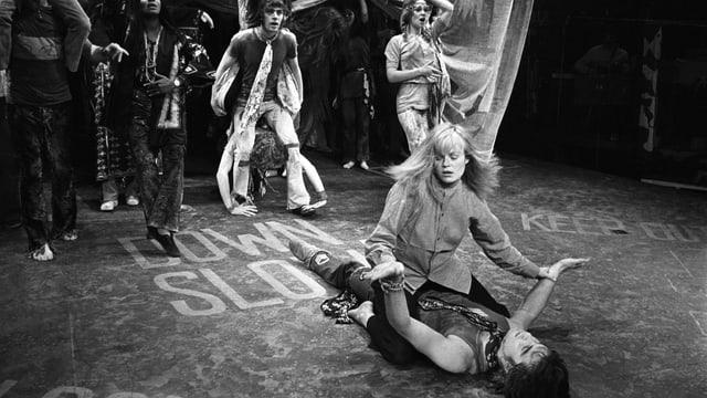 Eine Theaterbühne: Eine Frau sitzt auf einem Mann.