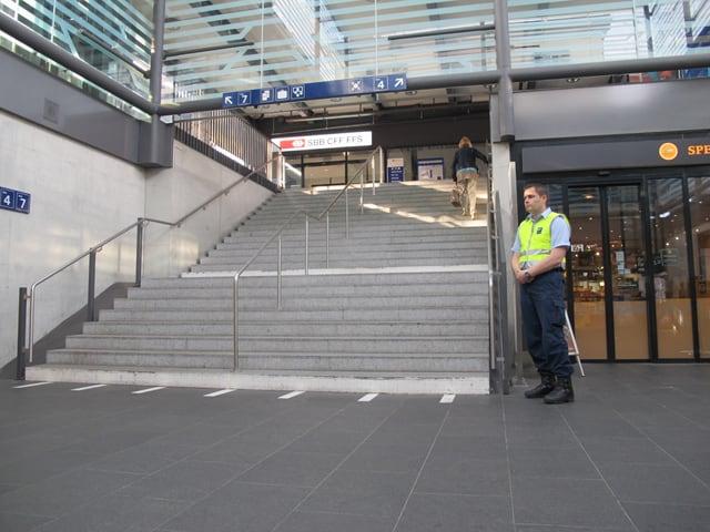 Securitas-Mitarbeiter in gelber Weste wartet unten an der Treppe.