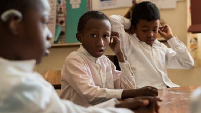 Drei hör- oder sehbehinderte Kinder in der Schule.