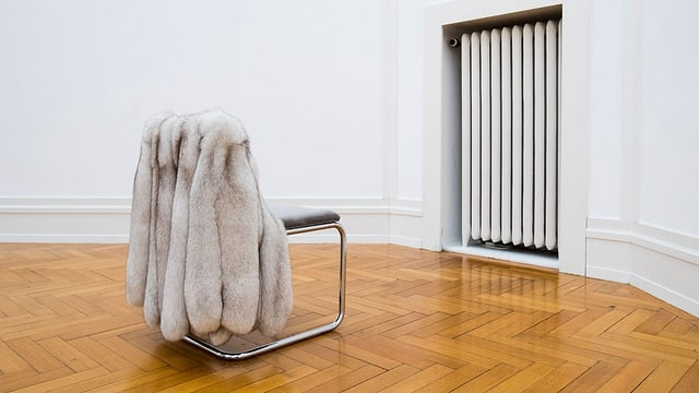 Ein leerer Stuhl mit einem Pelzmantel blickt in Richtung einer Wand mit einem Heizkörper.