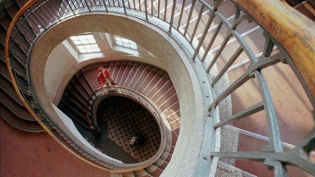 Eine Frau in rotem Pulli geht eine schneckenförmig gewundene Treppe hoch.