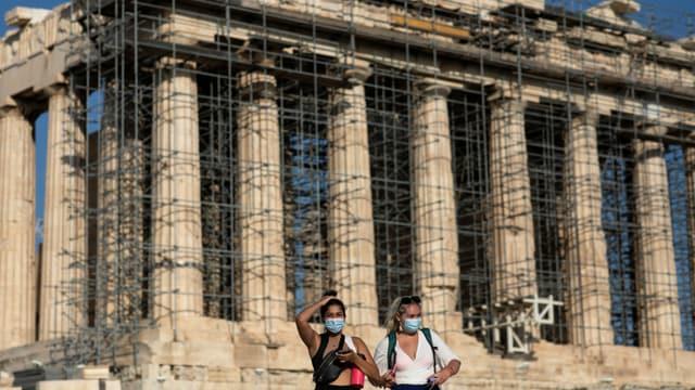 Zwei Frauen mit Maske vor der Akropolis.