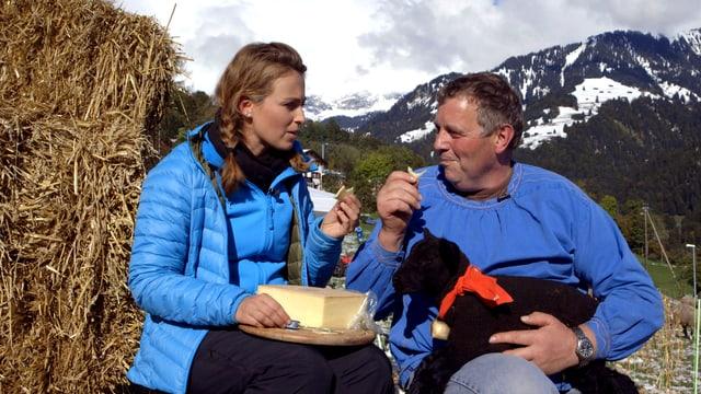 Die beiden Personen sitzen vor einem Heuballen und essen Käse. Auf dem Schoss von Herrn Jegen sitz ein schwarzes Lamm.