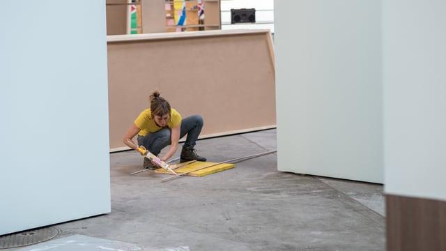 Eine Frau leimt Platten zusammen.