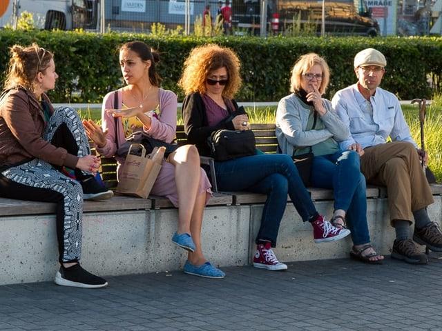 Fünf Menschen, vier Frauen und ein Mann, sitzen nebeneinander auf einer Bank.