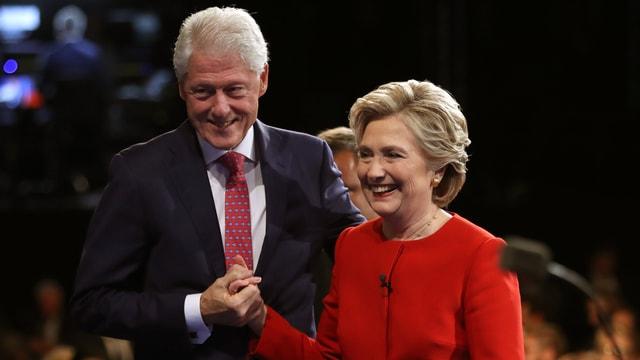 Bill und Hillary Clinton nach einer Wahlveranstaltung, halten sich die Hand und lächeln.