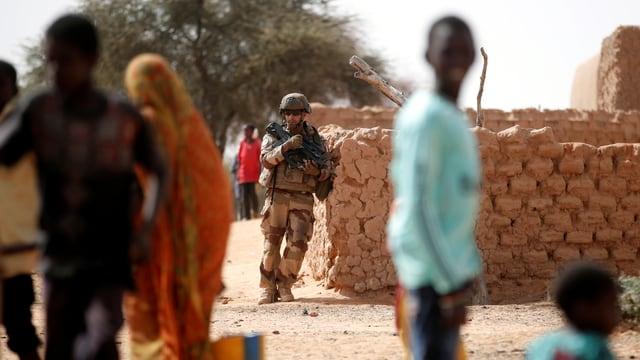 Ein französischer Soldat steht bewaffnet an einer Mauer, Dorfbewohner gehen ihren Beschäftigungen nach.