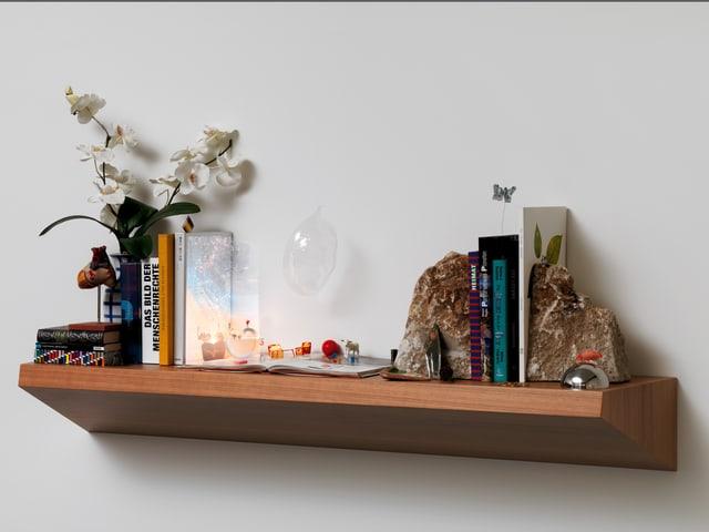 Ein Wandtablar mit Büchern, Orchideen und weiteren Gegenständen.