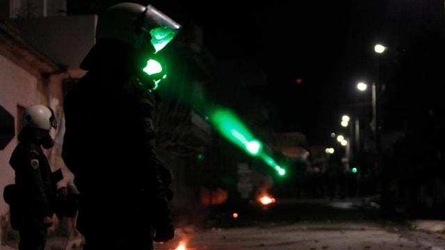 Ein Demonstrant blendet einen Polizisten in Kampfmontur mit einem Laserpointer.