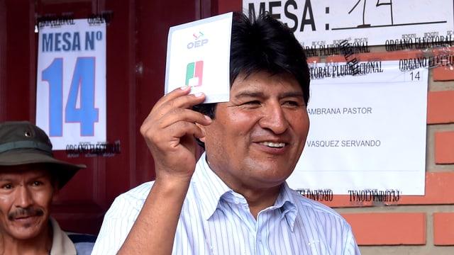 Evo Morales, Boliviens amtierender Staatspräsident möchte zum 4. Mal Präsident werden. Er hält vor einem Wahllokal in Villa 14 de Septiembre seinen Wahlzettel hoch und lacht.