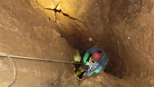 Eine Person wird in eine Höhle abgeseilt.