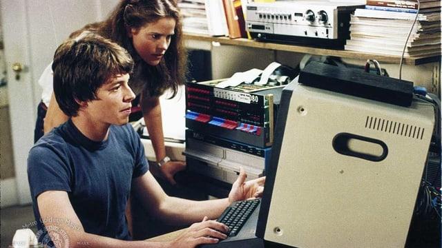 Ein junger Mann und eine junge Frau schauen in einen Bildschirm.