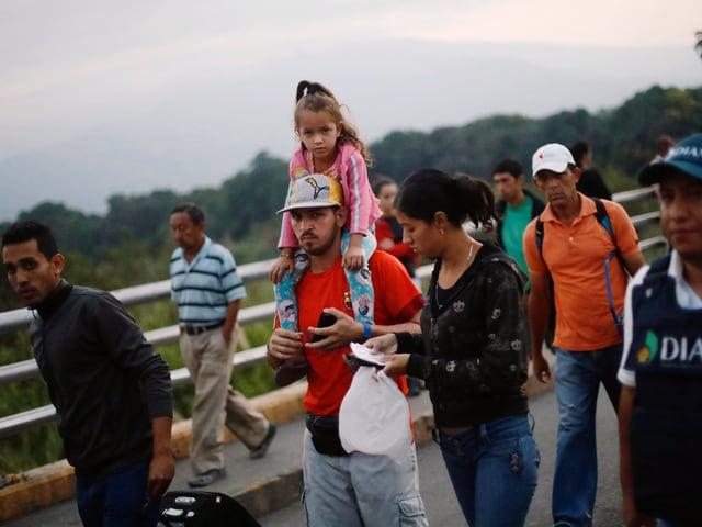 Eine kleinere Gruppe von venezolanischen Flüchtlingen läuft neben einem Brückengeländer. Ein Mann trägt ein Mädchen auf der Schulter.