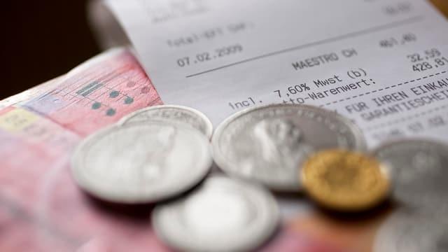 Ein Kassenzettel und Geldmünzen.