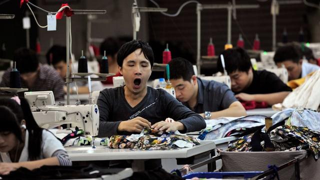 Chinesische Näherinnen und Näher in einer Fabrik, einer der Näher gähnt.