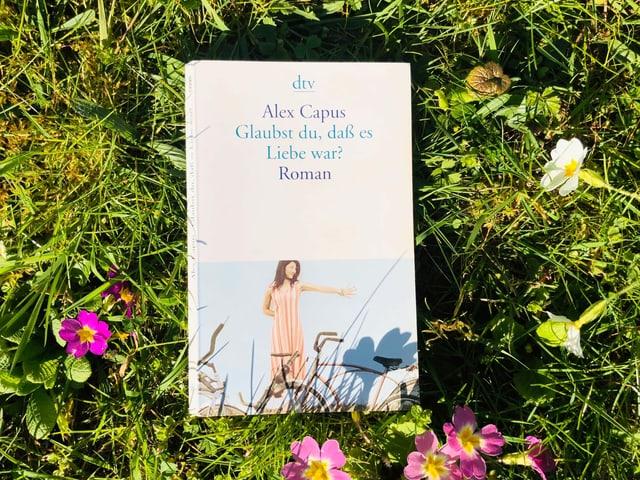 Alex Capus Roman «Glaubst Du, dass es Liebe war» liegt auf Gras