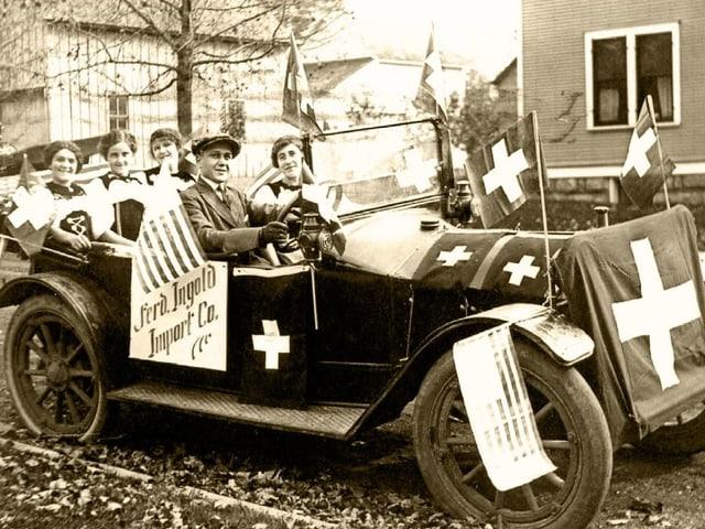 Ein Archivbild: Personen in einem alten Auto mit Schweizer Flaggen