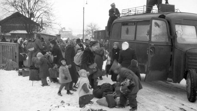 Schwarz-Weiss-Foto: Menschen steigen in einen Lieferwagen.
