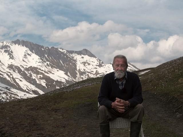 Mann sitzt auf einem Stuhl, im Hintergrund verschneite Berge.