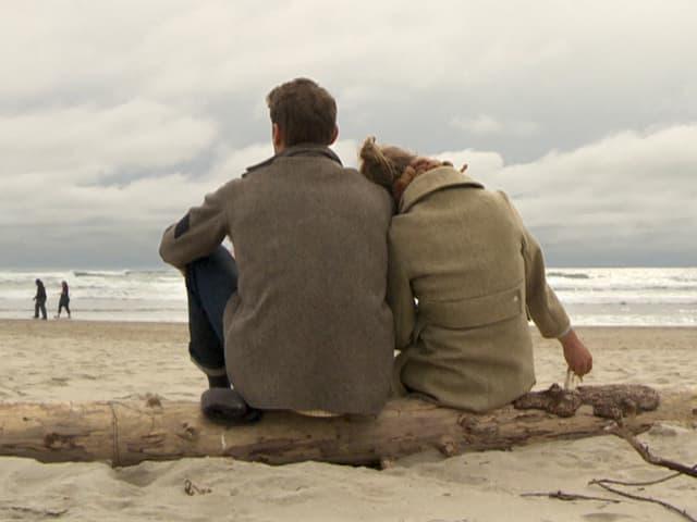 Von hinten photographiertes Liebespaar, das auf einem Baumstamm am Strand sitzt.